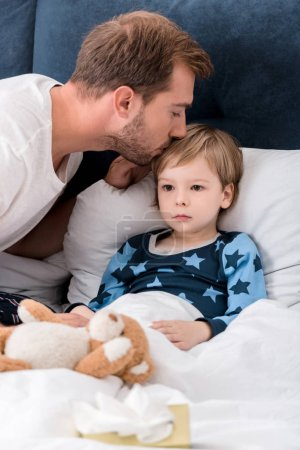 father checking sons temperature with lips while he lying in bed