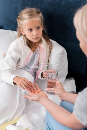cropped shot of mother giving pills and water to her sick daughter in bed