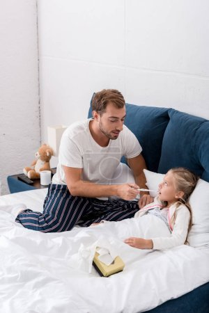 young father checking daughters oral temperature while she lying in bed