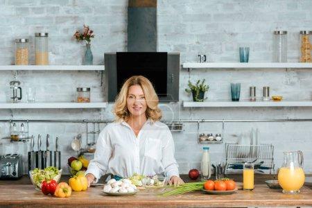 Foto de Feliz mujer adulta con varias verduras frescas en la mesa de la cocina mirando a cámara - Imagen libre de derechos