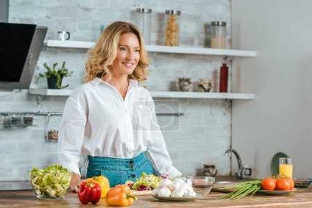 Photo for Beautiful adult woman with various fresh vegetables on kitchen table looking away - Royalty Free Image