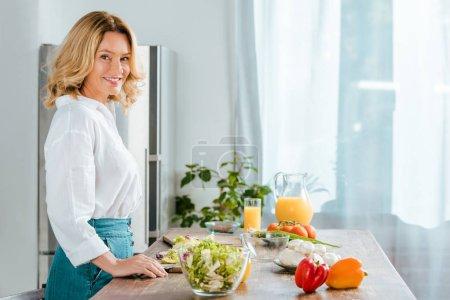 Photo pour Vue latérale d'une femme adulte heureuse regardant la caméra tout en faisant la salade à la cuisine - image libre de droit