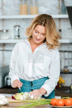 attractive adult woman cutting lettuce for salad at kitchen