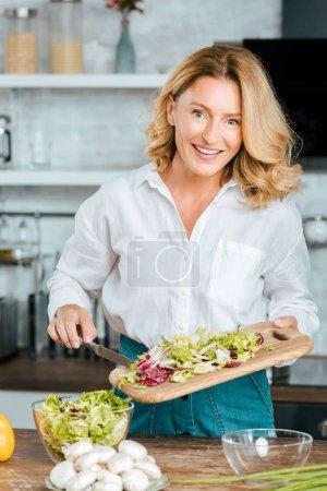 happy adult woman making healthy salad at kitchen and looking at camera