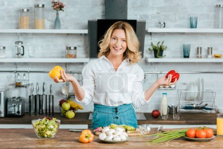 beautiful adult woman with bell peppers looking at camera while making salad at kitchen