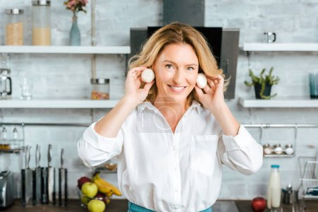 happy adult woman holding mushrooms near ears like earrings and looking at camera