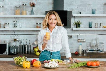 Photo pour Belle femme adulte le jus d'orange pendant la cuisson à la cuisine et en regardant de caméra - image libre de droit