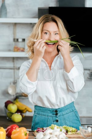 funny adult woman attaching leek like mustache at kitchen and looking at camera