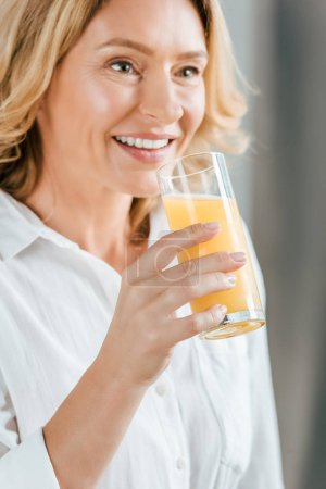 close-up portrait of beautiful adult woman drinking orange juice