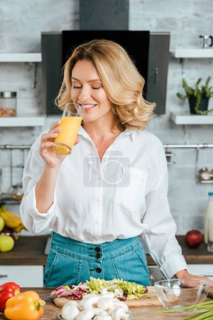 Photo for Beautiful adult woman drinking orange juice while cooking at kitchen - Royalty Free Image