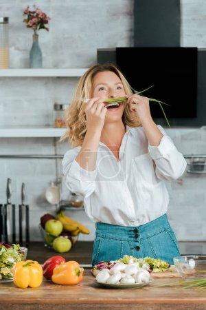 laughing adult woman attaching leek like mustache at kitchen