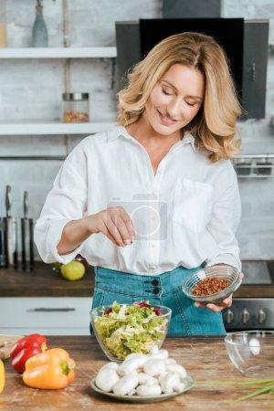 Photo pour Belle femme adulte déversant épice de laitue dans un bol à la cuisine - image libre de droit