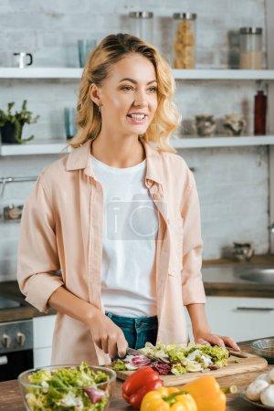 couper la laitue jeune femme attirante pour salade à la cuisine et de la recherche.