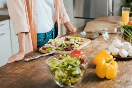 Photo for Cropped shot of woman standing near table with vegetables for salad at kitchen - Royalty Free Image