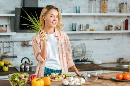 Photo for Smiling young woman with leek looking at camera while cooking at kitchen - Royalty Free Image
