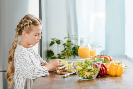 Photo for Side view of concentrated little child making salad at kitchen - Royalty Free Image