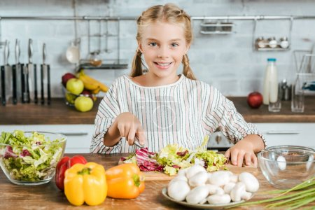 Photo for Happy little child cutting lettuce for salad at kitchen and looking at camera - Royalty Free Image