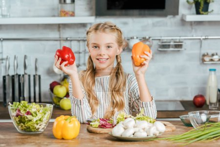 Photo for Smiling little child with bell peppers looking at camera while making salad at kitchen - Royalty Free Image