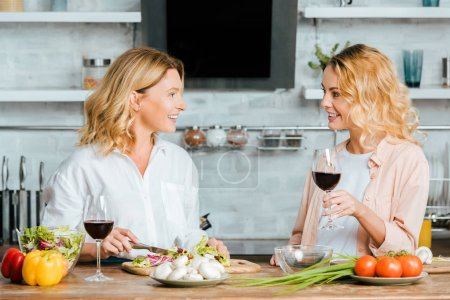 mature mother and adult daughter with glasses of red wine cooking together and chatting at kitchen