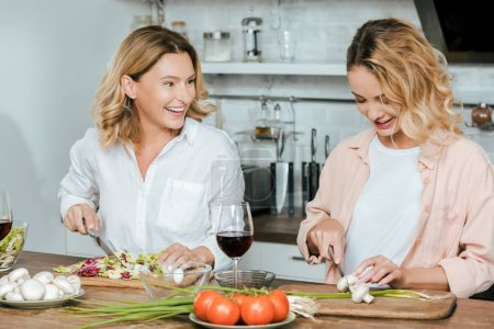 happy mature mother and adult daughter making salad together at kitchen