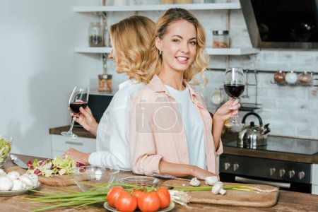 mature mother and smiling adult daughter with glasses of red wine standing back to back at kitchen