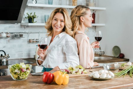 happy mature mother and adult daughter with glasses of red wine standing back to back at kitchen