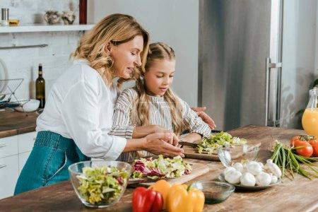 glückliche erwachsene Mutter und kleine Tochter, die zu Hause gemeinsam Salat schneiden