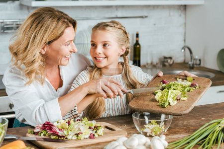 Photo for Happy adult mother and little daughter making salad together at home - Royalty Free Image