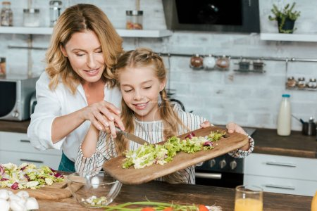 Photo for Beautiful adult mother and little daughter making salad together at home - Royalty Free Image