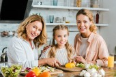 happy little child cutting vegetables for salad with mother and grandmother at home and looking at camera
