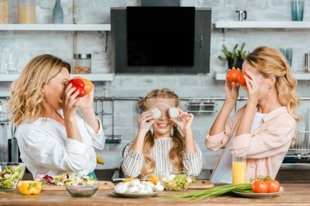 adorable little child covering eyes with food with mother and grandmother at home while cooking