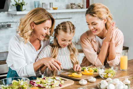 adorable little child cutting vegetables for salad with mother and grandmother at home