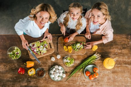 overhead view of child cutting vegetables for salad with mother and grandmother and looking at camera