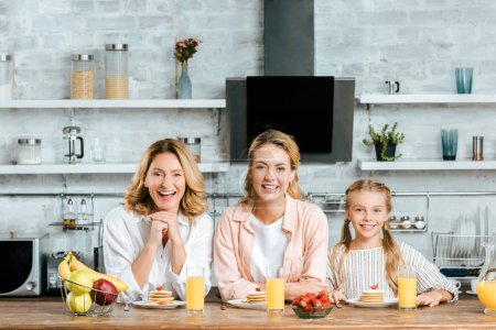 laughing three generations of women with pancakes and orange juice for breakfast at home looking at camera
