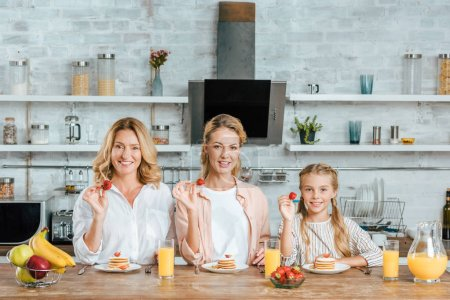 smiling three generations of women with pancakes and strawberries for breakfast at home looking at camera
