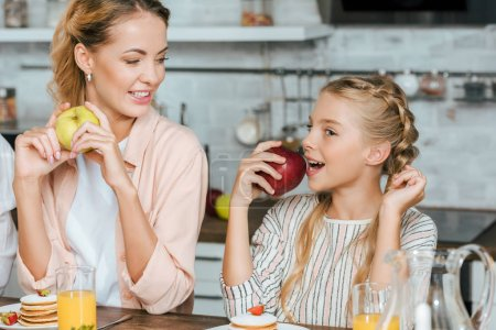 mother and daughter eating pancakes and apples at home