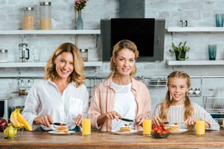 beautiful child with mother and grandmother eating pancakes for breakfast at home looking at camera