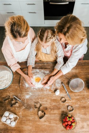 top view of child with mother and grandmother making dough with flour and egg together at home