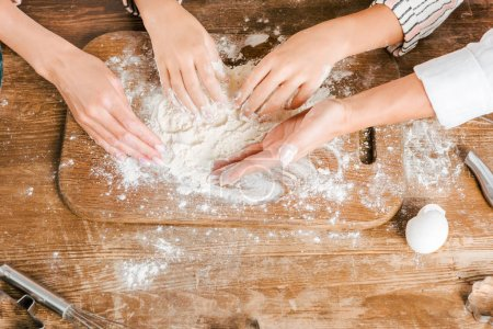 cropped shot of child and women making dough together on wooden board