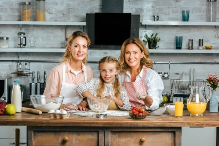smiling beautiful child with mother and grandmother making dough together at home and looking at camera
