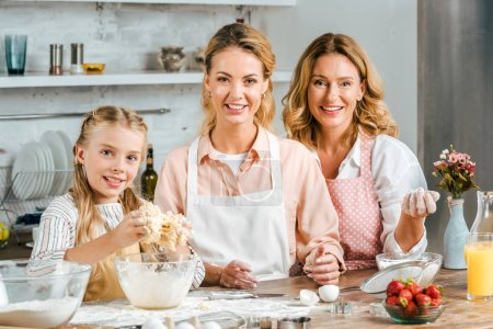 smiling child with mother and grandmother making dough together at home and looking at camera
