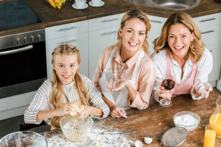 high angle view of smiling child with mother and grandmother making dough together at home and looking at camera