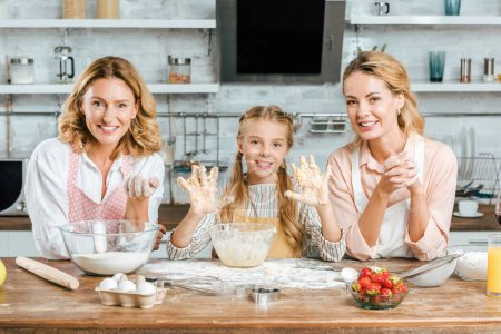 happy little child making dough with mother and grandmother at home and looking at camera