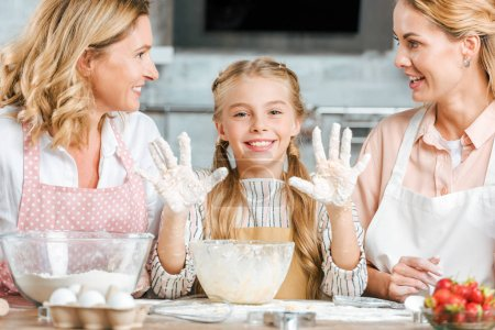 beautiful little child making dough with mother and grandmother at home and looking at camera