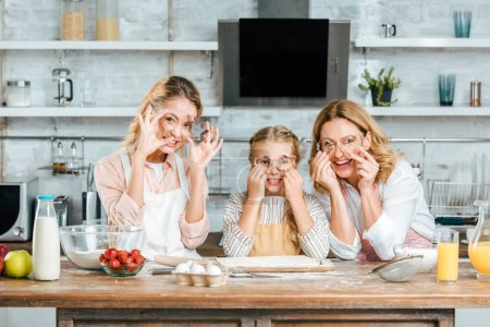 child with mother and grandmother looking at camera through dough cutters while cooking