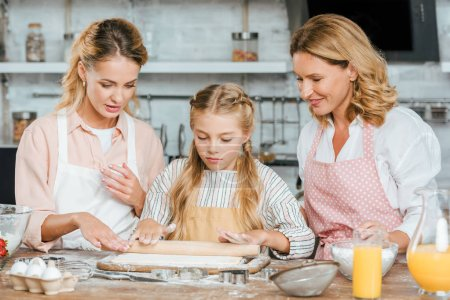 little child learning to make dough with mother and grandmother at home
