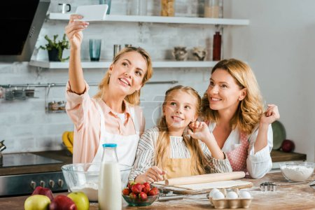 beautiful young  woman taking selfie with her mother and daughter while cooking at home