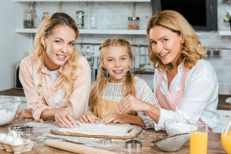 Photo for Beautiful happy three generations of women making dough together at home and looking at camera - Royalty Free Image