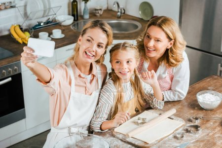 high angle view of woman taking selfie with her mother and daughter while cooking at home