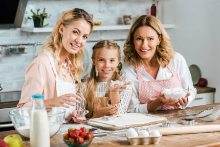 beautiful happy three generations of women making dough for cookies at home